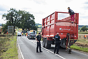 Police officers speak to an anti-HS2 activist who had occupied a trailer transporting wood chip in order to try to prevent or delay tree felling alongside the Fosse Way in connection with the HS2 high-speed rail link on 24th August 2020 in Offchurch, United Kingdom. The controversial HS2 infrastructure project is currently expected to cost £106bn and will destroy or significantly impact many irreplaceable natural habitats, including 108 ancient woodlands.