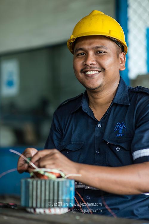 Repairing electrical motor at Bukit Maradja Mill, Pematang Siantar, Gunung Malela, Simalungun, Sumatra Utara, Indonesia.