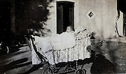 baby in an old stroller placed outside in the sunlight