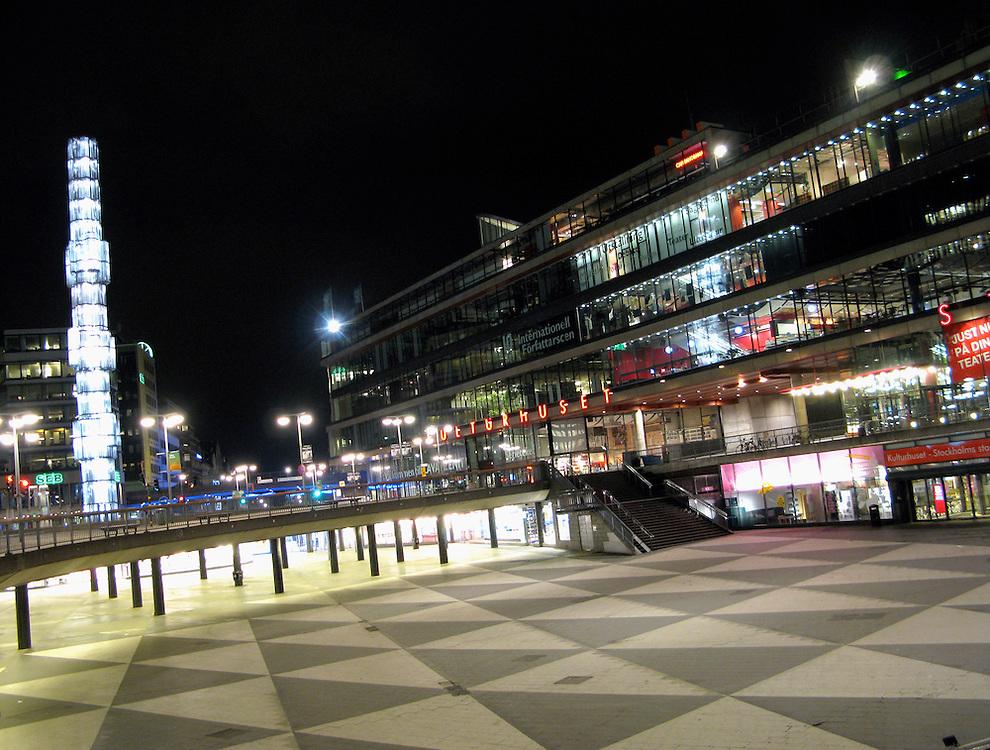 Vsita nocturna Sergels torg, con la Casa de la Cultura (Kultur Huset) al fondo, en el centro de Estocolmo (Suecia).