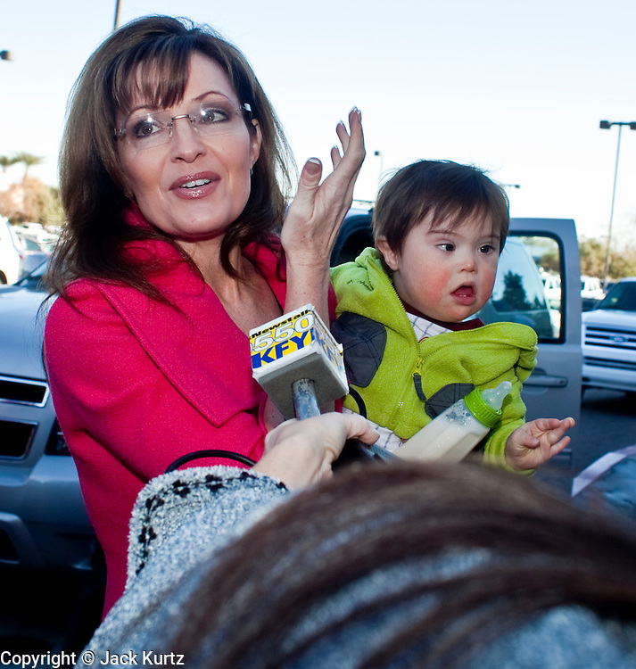 """Dec. 1, 2009 -- TEMPE, AZ: SARAH PALIN and her son, TRIG, arrive at the Costco in Tempe, AZ, Tuesday, Dec. 1. Former Alaska Governor Sarah Palin signed copies of her book, """"Going Rogue"""" at a Costco in Tempe, AZ, Tuesday. More than one thousand people showed up for the signing. About 150 of them spent the night at the store. Palin did not make any comments or speak to the address during her appearance in Tempe.  Photo by Jack Kurtz"""