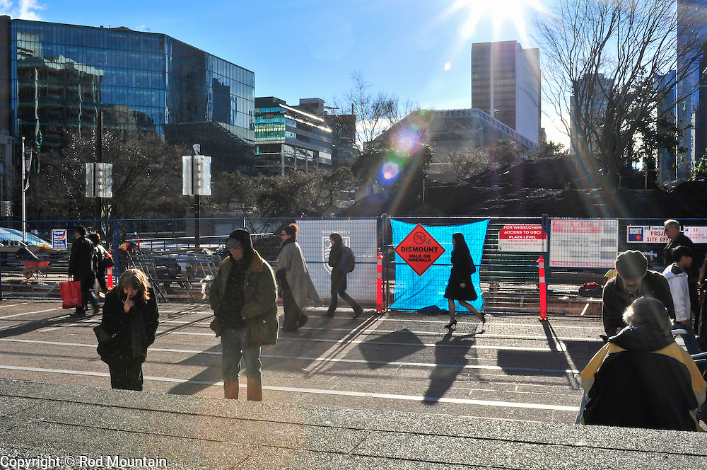 A woman stops to view artwork for sale near the steps of the Vancouver Art Gallery (Robson Street side) in Vancouver, BC