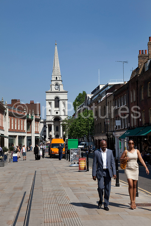 People walk along Market Street in Spitalfields, a shopping and market district in the City of London. Popular also as a hang out for city workers on their lunch breaks. At the end of 2005, after 18 years of sensitive preparation, the Spitalfields regeneration programme was completed. This regeneration has resulted in the creation of two new public spaces. Christ Church, Spitalfields is an Anglican church built between 1714 and 1729 to a design by Nicholas Hawksmoor. Situated on Commercial Street