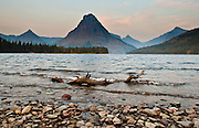 A nearby forest fire adds a smoky haze over Two Medicine Lake and Sinopah Mountain (8271 feet or 2521 meters), in Montana, in Glacier National Park, part of Waterton-Glacier International Peace Park.