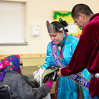 Students Kyia Dawes, center, the Miyamura High School Native American Princess and right, Adam Morris pass out gifts to the residents at McKinley Manor, Friday March 22 after they perform songs for them. Dawes and Morris are students at Miyamura High School and are part of the Native American Club.