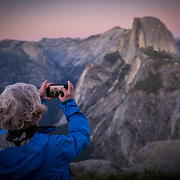 A lone photographer snap photos of Half Dome as it is lit up at sunset in this view from Glacier Point inside Yosemite National Park on Sunday, September 22, 2019 in Yosemite, California. (Alex Menendez via AP)
