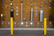 A display by a company selling wall-mounted and post lighting in south London. Vertical lines of the light fixtures seem to merge with the yellow security barriers that prevent instruders or ram raiders. Many of the lights are on, shining out on the street during daytime.