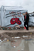 France. Refugees. Calais. So-called Jungle camp , partly under water after heavy rain. A refugee walks in front of a shelter with writing on it saying 'Lets go England GB'.