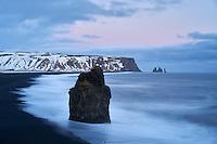Arnardrangur Sea Stack and Reynisfjara black sand beach after sunset in winter. South coast of Iceland.
