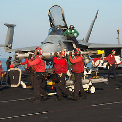 USS John C Stennis CVN-74 Aircraft Carrier.Pic Shows Flight and Hangar Deck personnel in the red shirts making sure the F-18 Super Hornets  aircraft are loaded withe correct weapons and ammunition