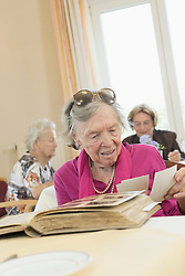 Senior woman watching photo album in rest home, Bavaria, Germany