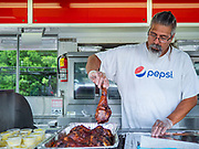 "26 JUNE 2020 - DES MOINES, IOWA: PAT GARCIA serves grilled turkey legs in the Turkey Time booth at Fair Food Friday in Des Moines. The 2020 Iowa State Fair, like many state fairs in the Midwest, has been cancelled this year because of the COVID-19 (Coronavirus) pandemic. The cancellation of the fair left many small vendors stranded with no income. Some of the fair food vendors in Iowa started ""Fair Food Fridays"" on a property a few miles south of the State Fairgrounds. People drive up and don't leave their cars while vendors bring them the usual midway fare; corndogs, fried tenderloin sandwiches, turkey legs, deep fried Oreos, lemonaide and smoothies. Fair Food Friday has been very successful. The vendors serve 450-500 people per Friday and during the lunch rush people wait in line in their cars 30 - 45 minutes to place an order.      PHOTO BY JACK KURTZ"