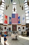 East Meadow, New York, USA. May 25, 2019. At the Nassau County Veterans Memorial Museum, a boy holds a small American flag as his family looks at miliary memorabilia displayed under the American Flag and military flags of the United States Armed Forces - Army, Navy, Marine Corps, Air Force, Coast Guard - suspended high in the ceiling, during Saturday of Memorial Day Weekend at Eisenhower Park on Long Island.