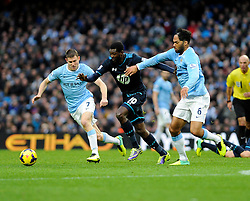 Tottenham Hotspur's Emmanuel Adebayor is chased down by Manchester City's Joleon Lescott and Manchester City's James Milner - Photo mandatory by-line: Dougie Allward/JMP - Tel: Mobile: 07966 386802 24/11/2013 - SPORT - Football - Manchester - Etihad Stadium - Manchester City v Tottenham Hotspur - Barclays Premier League