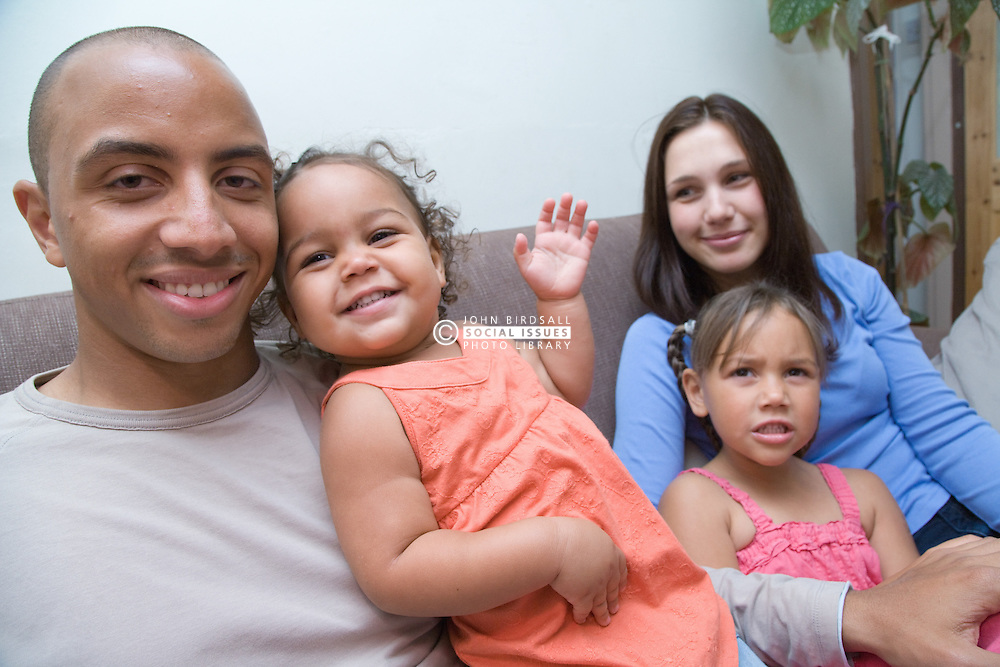 Young family sitting on the sofa together,
