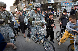 Sgt. Major George Crisostomo rides a local kid's bike in jest while patrolling with other members of the 1st Infantry, 17th Regiment, Mosul, Iraq, Dec. 16, 2005. This is part of an effort to provide security in preparation for Iraq's first post-Saddam parliamentary elections. The western sector is home to Mosul's primarily Sunni population, which has been resistant to the American presence in Iraq.