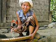 """An elderly Laoseng minority woman preparing rice for dinner outside her home in remote and roadless Ban Watai, Phongsaly Province, Lao PDR.  The villagers of Ban Watai wait to hear when and where they will be relocated and joined with three other Laoseng villages following the construction of the Nam Ou Cascade Hydropower Project Dam 5. The Nam Ou river connects small riverside villages and provides the rural population with food for fishing. It is a place where children play and families bathe, where men fish and women wash their clothes. But this river and others like it, that are the lifeline of rural communities and local economies are being blocked, diverted and decimated by dams. The Lao government hopes to transform the country into """"the battery of Southeast Asia"""" by exporting the power to Thailand and Vietnam."""