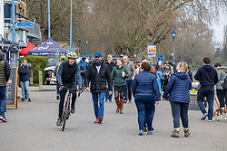 """© Licensed to London News Pictures. 28/03/2021. London, UK. Members of the public enjoy a stroll along the River Thames in Putney, South West London ahead of the end of the """"Stay at Home"""" advice from tomorrow with temperatures expecting to reach up to 23c next week. On Monday 29 March, the """"Stay at Home"""" advice will end with people being allowed to meet up within the """"rule of six"""". Playing golf, tennis and organised outdoor sports will also be allowed as England starts to unlock after a year of Covid-19 restrictions. Photo credit: Alex Lentati/LNP"""