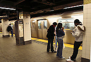 USA, NY, New york city, Manhattan, People waiting at a Subway station while a train rushes through