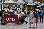 Local residents and visitors shop and relax in the town centre, some choosing to wear face coverings outside, on 14th July 2021 in Windsor, United Kingdom. The UK government announced on 12th July that England will move to the final stage of easing Covid-19 restrictions on 19th July, with almost all legal restrictions on social contact removed, but they also advised the public to exercise caution given that the current wave driven by the Delta variant is not expected to peak until mid-August.