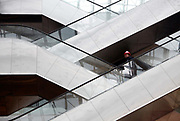 A worker walks down an escalator at the nearly completed new terminal of the Hongqiao Airport in Shanghai, China on 21 January 2010.  The new terminal is a part of the larger Hongqiao Transportation Hub that will combine air, high-speed rail, and maglev links.