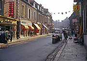 Line of shops with people brushing the street leading to market place, thought to be Quimper, Brittany, France in 1974