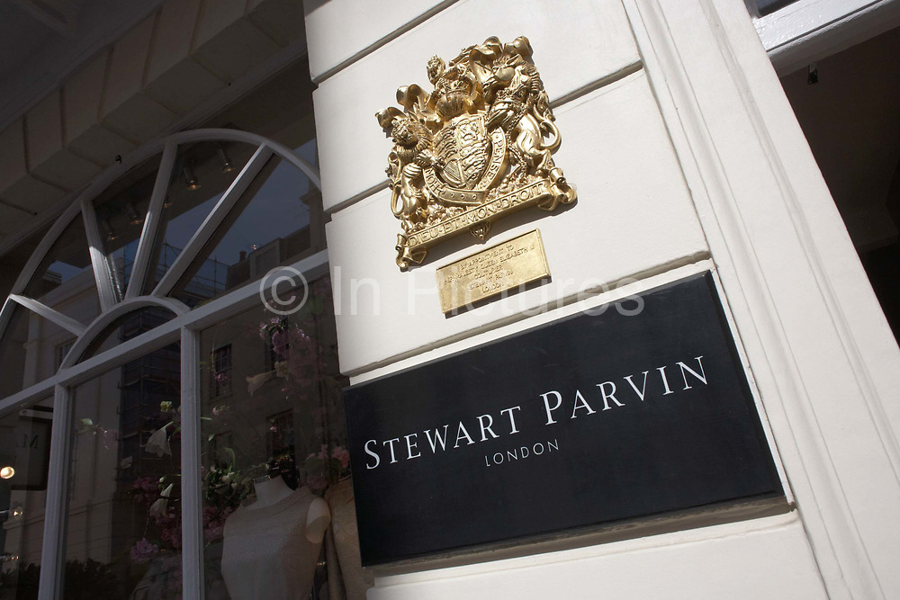 With a prominent Royal Warrant as couturier to Her Majesty the Queen, the fashion house Stewart Parvin's boutique name is seen outside 14 Motcomb Street in exclusive Belgravia, London. Royal Warrants are a mark of recognition to individuals or companies who have supplied goods or services for at least five years to HM The Queen, HRH The Duke of Edinburgh or HRH The Prince of Wales. There are around 850 Royal Warrant Holders representing a huge cross-section of trade and industry. Warrant Holders may display the relevant Royal Arms and the legend 'By Appointment' on their products, premises, stationery, vehicles and advertising but must adhere to strict guidelines for its proper use.<br /> <br /> <br /> <br /> <br /> Motcomb Street SW1