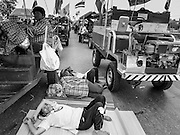 21 FEBRUARY 2014 - KHLONG CHIK, PHRA NAKHON SI AYUTTHAYA, THAILAND: Women sleep on the pavement at a roadblock set up by Thai farmers on Highway 32. About 10,000 Thai rice farmers, traveling in nearly 1,000 tractors and farm vehicles, blocked Highway 32 near Bang Pa In in Phra Nakhon Si Ayutthaya province. The farmers were traveling to the airport in Bangkok to protest against the government because they haven't been paid for rice the government bought from them last year. The farmers turned around and went home after they met with government officials who promised to pay the farmers next week. This is the latest blow to the government of Yingluck Shinawatra which is confronting protests led by anti-government groups, legal challenges from the anti-corruption commission and expanding protests from farmers who haven't been paid for rice the government bought.    PHOTO BY JACK KURTZ