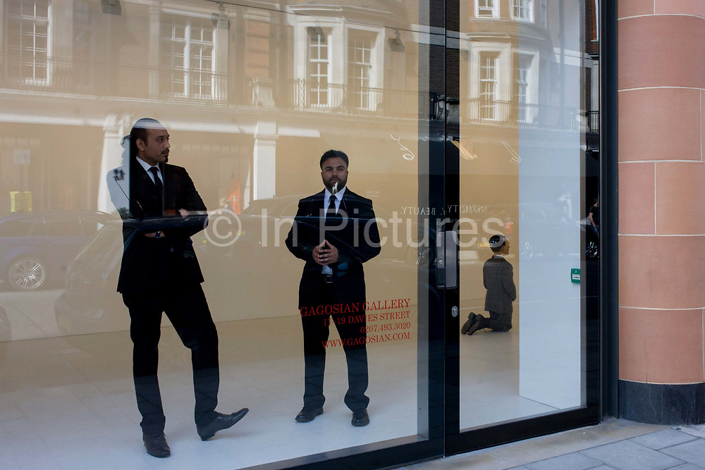 Staff at the Gagosian Art Gallery in Davies Street, London stand in the window with a kneeling Hitler called La Fine di Dio by Maurizio Cattelan. The controversial artwork is featured in this Mayfair gallery window and the employees stand prominently to avoid trouble.