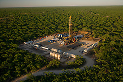 Aerial view of onshore oil drilling rig work site surrounded by trees.