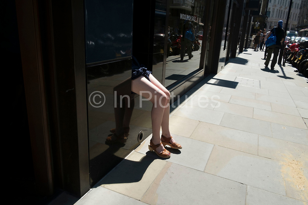 Pair of womans legs protruding from a gap in a shopfront wall where she is sitting, hiding the rest of her body in London, England, United Kingdom.