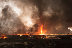 Licensed to London News Pictures. 08/11/2016. Qayyarah, Iraq. Smoke and a flaming tornado are seen at a burning oil facility in the town of Qayyarah, Iraq. Oil wells in and around the town of Qayyarah, Iraq, we set alight in July 2016 by Islamic State extremists as the Iraqi military began an offensive to liberated the town.<br /> <br /> For two months the residents of the town have lived under an almost constant smoke cloud, the only respite coming when the wind changes. Those in the town, despite having been freed from ISIS occupation, now live with little power, a water supply tainted with oil that only comes on periodically and an oppressive cloud of smoke that coats everything with thick soot. Many complain of respiratory problems, but the long term health implications for the men, women and children living in the town have yet to be seen. Photo credit: Matt Cetti-Roberts/LNP