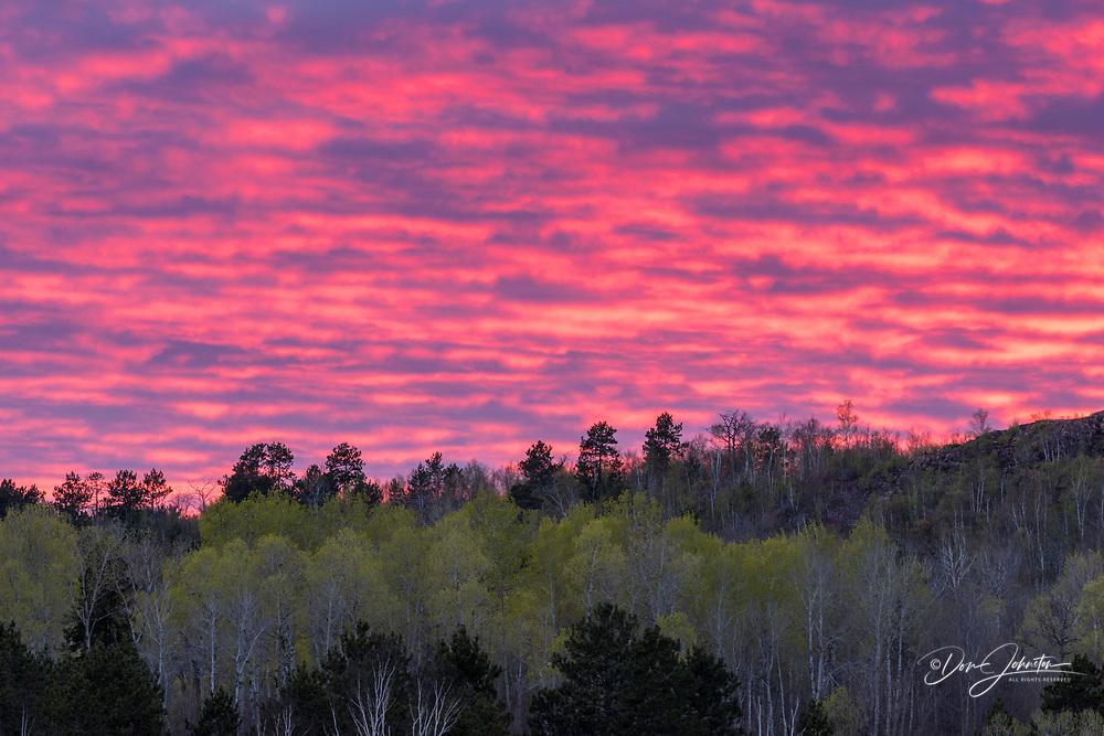 Sunset skies over a ridgeline of spring trees, Greater Sudbury, Ontario, Canada