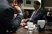 businessmen checking messages on their smartphone while sitting in a coffee bar
