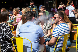 © Licensed to London News Pictures. 12/06/2021. LONDON, UK. A diner exhales a vape cigarette in Soho.  Scientific advisers to the UK government have called for a delay to the complete lifting of coronavirus lockdown restrictions on 21 June, possibly by four weeks, to allow scientists to assess the link between rising numbers of Covid-19 cases (mainly the newly identified Delta variant) and hospital admissions.  Photo credit: Stephen Chung/LNP