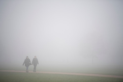 © Licensed to London News Pictures. 17/12/2016. London, UK. Visitors to Hyde Park walk in the fog.  Parts of the UK are swathed in thick fog this morning. Photo credit: Ben Cawthra/LNP