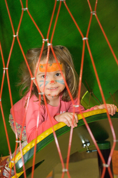 United States, Washington, Bellevue, girl with face paint climbs on play structre at KidsQuest Children's Museum.  MR, PR