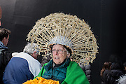 New York, NY, USA-27 March 2016. A woman wears an elaborate hat made to look like a giant dandelion ready to burst out in seeds in the annual Easter Bonnet Parade and Festival.
