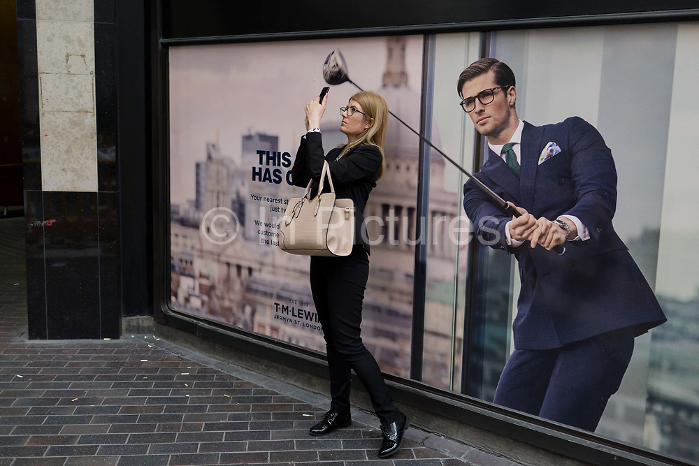 A lady pauses to take a picture of the nearby Lloyds Building next to a closed shop poster featuring a businessman enjoying leisure time on the golf course wearing a blue suit - a favoured style and colour of menswear in the City of London, the capitals financial district - aka the Square Mile, on 29th August 2018, in London, England.