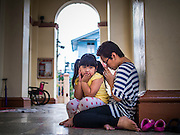 15 FEBRUARY 2015 - BANGKOK, THAILAND: A woman and her daughter sit in front of the sanctuary during Sunday mass at Santa Cruz Catholic Church in the Kudeejeen neighborhood in Bangkok. Santa Cruz church was established in 1770  and is one of the oldest and most historic Catholic churches in Thailand. The church was originally built by Portuguese soldiers allied with King Taksin the Great. Taksin authorized the church as a thanks to the Portuguese who assisted the Siamese during the war with Burma. Most of the Catholics in the neighborhood trace their family roots to the original Portuguese soldiers who married Siamese (Thai) women. There are about 300,000 Catholics in Thailand in about 430 Catholic parishes and about 660 Catholic priests in Thailand. Thais are tolerant of other religions and although Thailand is officially Buddhist, Catholics are allowed to freely practice and people who convert to Catholicism are not discriminated against.      PHOTO BY JACK KURTZ