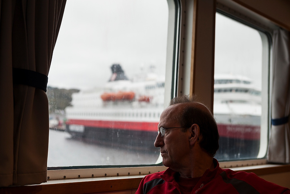 Parmenter Welty looks out the window of the Bodo - Moskenes ferry docked in the port in Bodo, Norway. A Hurtigruten cruise ship is visible outside.