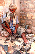 INDIA, RAJASTHAN man repairing shoes on sidewalk in Jaisalmer