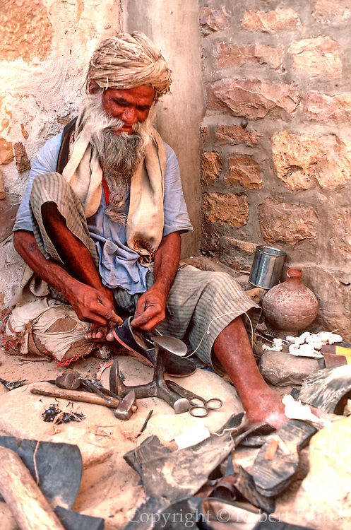 INDIA, RAJASTHAN man repairing shoes on sidewalk in Jaisalmer