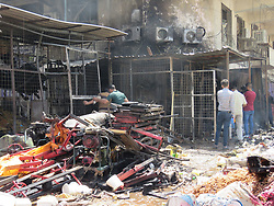 Aug. 28, 2017 - Baghdad, Iraq - People check the damage of a building at the scene of a car bomb explosion at Jamila wholesale market in Baghdad's Shiite district of Sadr city, Iraq. The death toll from the car bomb explosion at a busy market area in eastern Baghdad on Monday rose to 12 people killed and 24 others wounded, an Interior Ministry source told Xinhua.  (Credit Image: © Khalil Dawood/Xinhua via ZUMA Wire)