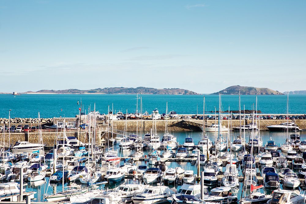 Boats and yachts moored up in St Peter Port harbour with views of Sark and Herm islands beyond, popular with tourists for day trips from Guernsey, CI