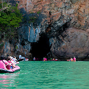 Tourists enter cave on canoes in the national marine park of Phang Nga Bay, Thailand