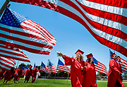 A graduating senior reaches to touch one of the flags lining the football field as the Garden Grove High School graduation ceremony begins  in Garden Grove, CA.