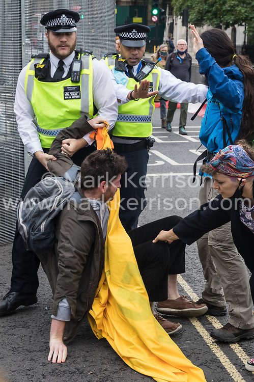 Police officers prevent climate activists from Extinction Rebellion from joining fellow activists who had glued themselves to the pavement outside the Houses of Parliament on 3 September 2020 in London, United Kingdom. Extinction Rebellion activists are attending a series of September Rebellion protests around the UK to call on politicians to back the Climate and Ecological Emergency Bill (CEE Bill) which requires, among other measures, a serious plan to deal with the UK's share of emissions and to halt critical rises in global temperatures and for ordinary people to be involved in future environmental planning by means of a Citizens' Assembly.