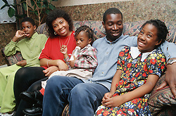 Portrait of couple and young children sitting on sofa smiling,