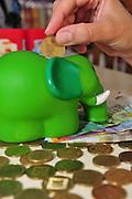Saving coins in a piggy bank